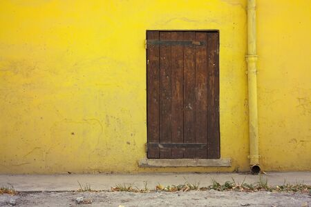 country house style: Yellow house wall and an old wooden door Stock Photo