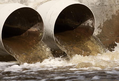 soil pollution: Toxic water from the sewer running to the river Stock Photo