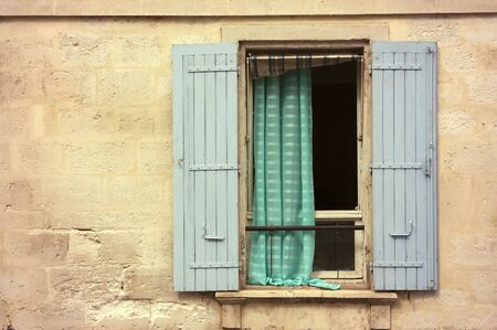 iron curtains: Old wooden window with blue shutter in a stone house