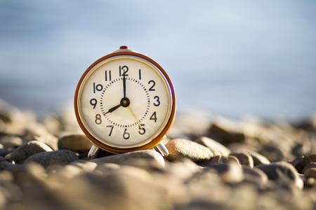 pepples: Time symbol - old alarm clock on the sea beach