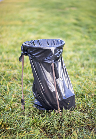 trash bag: Plastic trash bag in a green park to maintain the environment clean Stock Photo