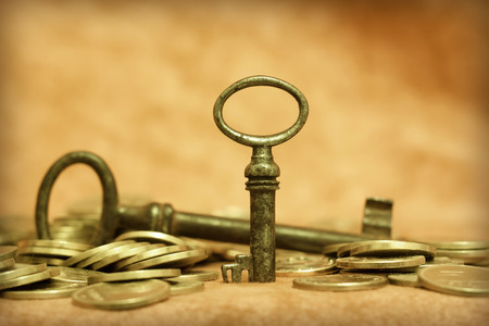 key success: Gold money with an antique key - success and solution concept Stock Photo