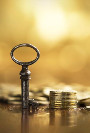 Business success concept - key and golden money coins in vertical Foto de archivo