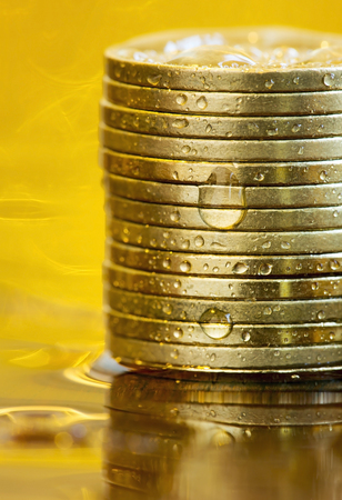 Business success concept - vertical photo of gold money coins with water drops Imagens