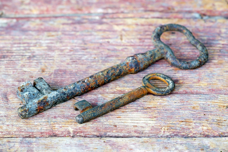 Solution, help concept - two rusty keys lying on a wooden board