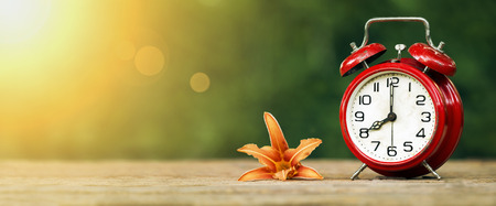 Daylight savings, spring forward concept - web banner of a red alarm clock and flower