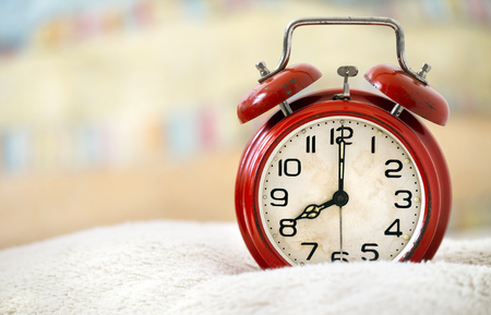 Good morning, wake up, awakening concept - retro red alarm clock in the bed - web banner with copy space