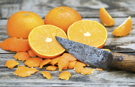 Whole and peeled fresh yellow mandarins with a sharp rustic knife on wooden background