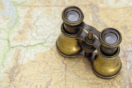 Vintage rustic binoculars standing on a map, background with copy space