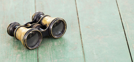 Search concept, old binoculars on a wooden table, web banner with copy space 写真素材