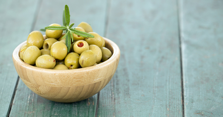 Web banner of green olives on wooden background with copy space