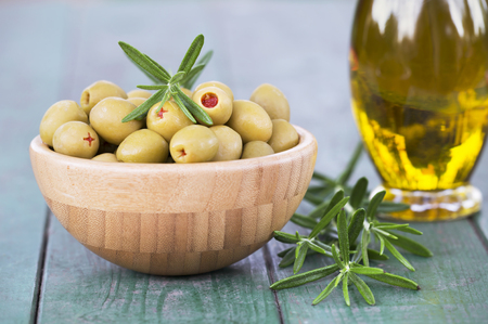 Fresh healthy green olives with rosemary and virgin oil in a bottle on wooden table