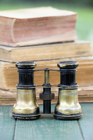 Search concept, old binoculars and books on a wooden table