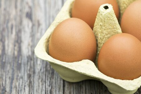 Close-up of fresh eggs on a wooden table with copy space