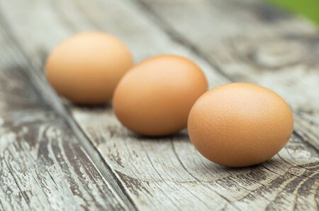 Breakfast ingredient, close-up of fresh eggs on a wooden table