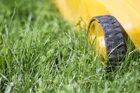 Close-up of a lawn mower wheel on green lawn grass, gardening equipment, background with copy space