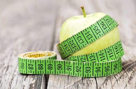 Weight loss, diet concept - green apple with tape measure on a wooden background Stock Photo