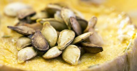 Close-up of roasted yellow pumpkin seeds, healthy eating, vegetarian snack food banner