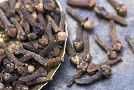 Organic spices, group of cloves, close-up on metal background