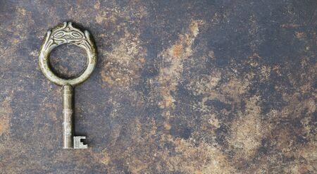 Antique rusty ornate key on grunge metal background, escape room concept, web banner with copy space