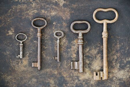 Escape room concept, group of antique keys on rusty metal background