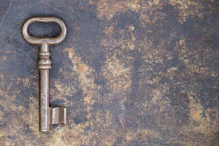 Antica chiave ornata arrugginita su sfondo metallico grunge, concetto di escape room Archivio Fotografico