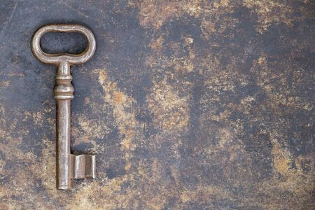 Antique rusty ornate key on grunge metal background, escape room concept