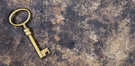 Old vintage golden key on a rusty grunge metal background, web banner with copy space, escape room concept