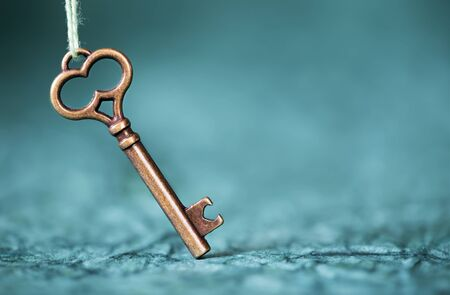 Escape room concept. Vintage key on abstract blue background with text copy space