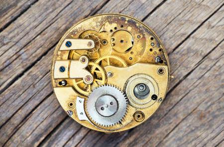 Antique metal pocket watch clockwork with gears on wooden background