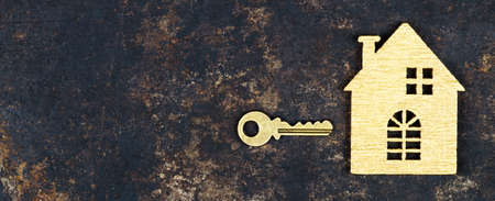 Buy new home, real estate concept, gold key and wooden house shape, web banner with copy space