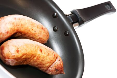 sausages in frying pan isolated on white background photo