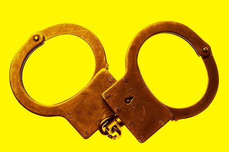 handcuffs on yellow background Stock Photo - 5530005