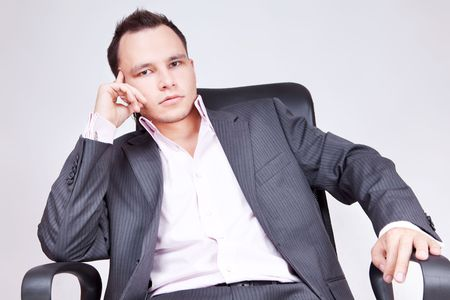 Portrait of business male model. Young businessman sitting on chair and thinking. photo