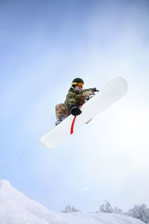 snowboarder jumping: Snowboarder jumping through air with blue sky.