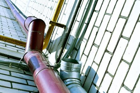 Storm pipes from a high-rise building of brown and metal color. Pipes for rainwater runoff. Sewer Zdjęcie Seryjne