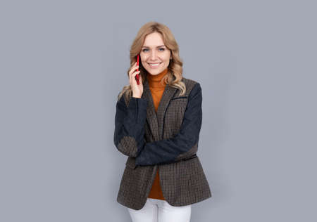Happy woman in casual fashion style talk on modern mobile phone grey background, communication