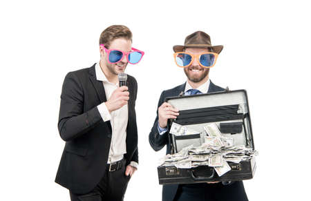 Happy emcee interview rich sponsor with money suitcase isolated on white, sponsoring Banque d'images