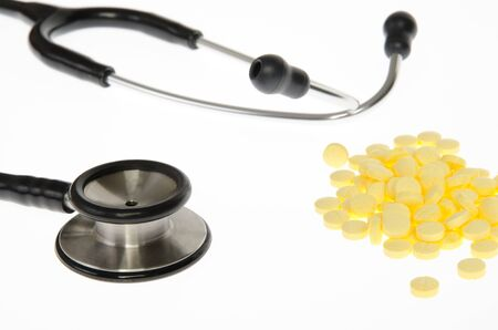 Stethoscope and medical pills tablets on white background. photo