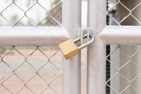 chain link fence and metal door with lock photo