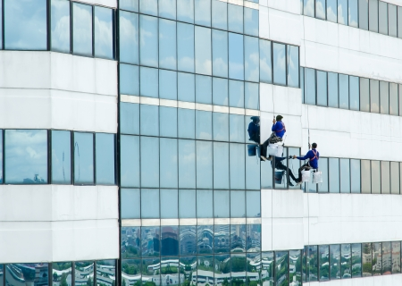 group of workers cleaning windows on building high tower