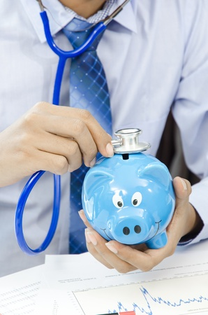 Man  holding Stethoscope to Pink Piggy Bank photo