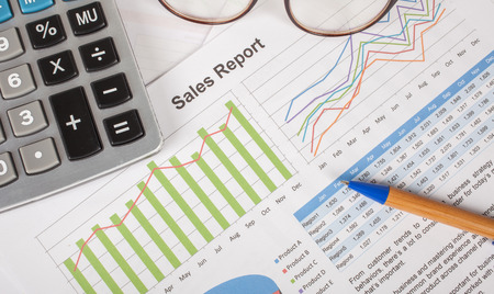 brand monitoring: sheet of  sales report with pen,and calculator