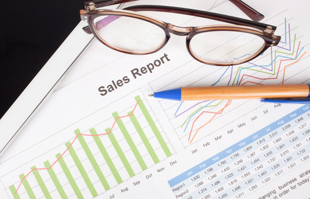 brand monitoring: sheet of  sales report with pen,and glasses on tablet Stock Photo