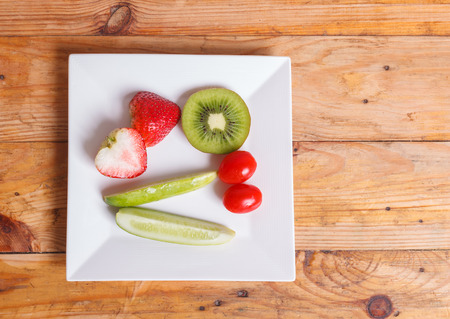 Fruit and vegetable salad in a bowl on wooden background,diet weight loss concept