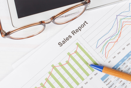 sheet of  sales report with pen,and glasses on tablet Stock Photo