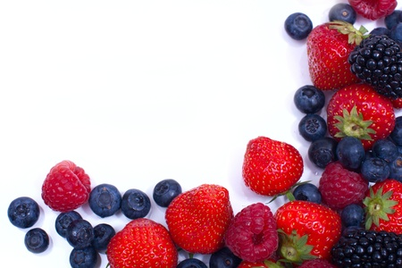 mixed fruit: angular frame of juicy, ripe strawberries, blueberries, raspberries and blackberries on a white background  space for text on the left
