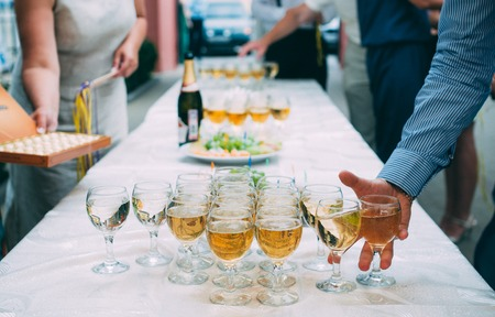 line lines luxury meeting: men s hand takes a glass of champagne at the wedding banquet Stock Photo