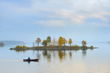 Fisherman swims around the island on the lake Stok Fotoğraf - 123698347