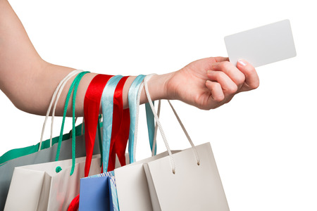 Frauenhand mit vielen Taschen und Kreditkarte auf weißem Hintergrund